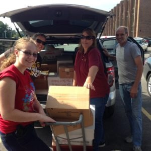 UPS volunteers filling their cars with boxes of books and supplies.